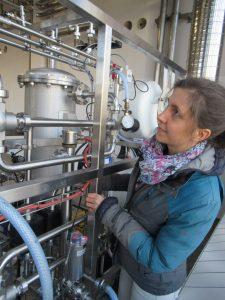 Abbildung 1: Franziska Strube, wissenschaftliche Mitarbeiterin am Lehrstuhl für Umweltgerechte Produktionstechnik, begutachtet die Pilotanlage zur adsorptiven CO2-Rückgewinnung.
